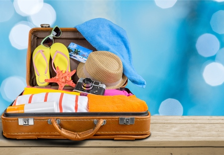 Retro suitcase with travel objects on wooden