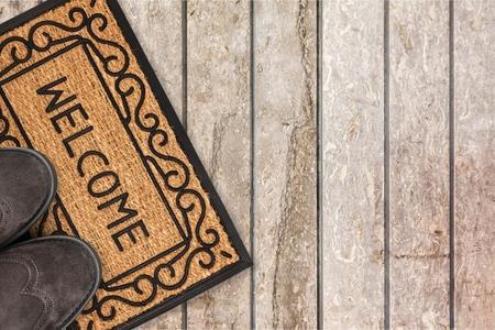 Bienvenida limpiando la alfombra de los pies con zapatos y