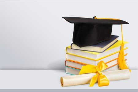 Birrete de graduación en la parte superior de la pila de libros sobre fondo blanco.