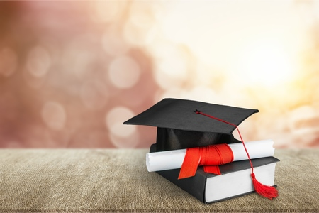 Graduation mortarboard on  book on  background