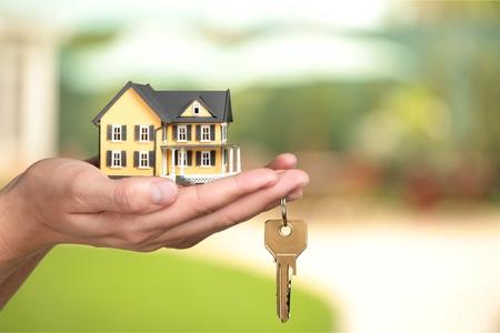 Geschäftsmann hält Hausmodell und Schlüssel, Real