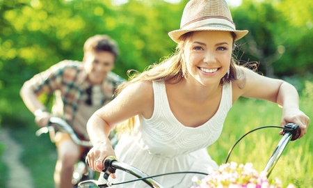 Happy young couple cycling through park