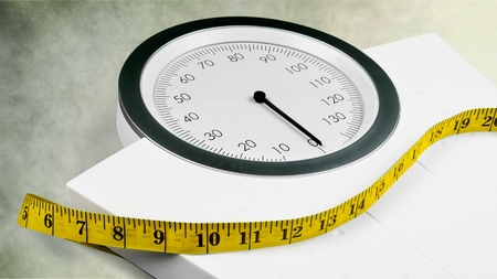 Bathroom scale with a measuring tape on background Archivio Fotografico