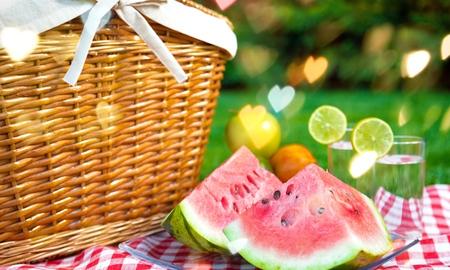 Cesta de picnic con sandía en la naturaleza