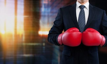 Hombre de negocios en traje gris con guantes de boxeo rojos