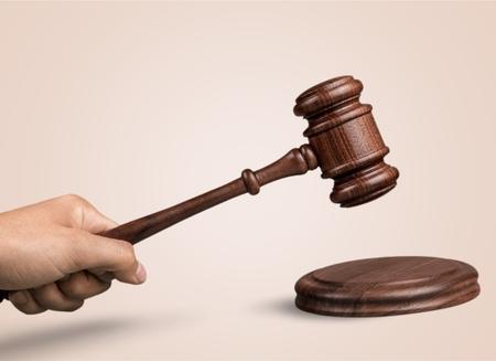 Męska ręka z drewnianym młotkiem sędziego na tle Zdjęcie Seryjne
