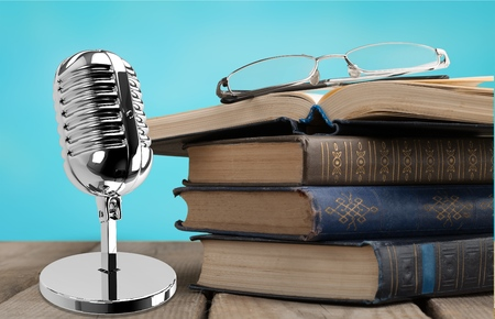 Education teaching concept : Retro microphone with many book put on wooden table isolated on blue background.          - Image