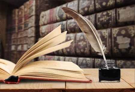 Old quill pen, books and vintage inkwell on wooden desk in the old office against the background of the bookcase and the rays of light. Conceptual background on history, education, literature topics.