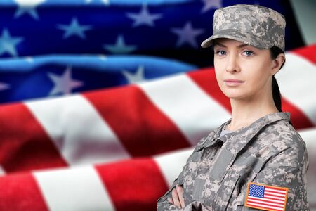 Portrait of female US army soldier on flag background
