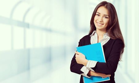 Young smiling woman holding blue notebook Stock Photo