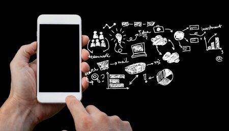 Manos humanas sosteniendo smartphone con iconos dibujados sobre fondo oscuro