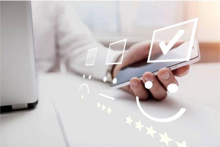 Geschäftsfrau, die Gesichtsemoticon auf dem Tastaturlaptop drückt/Kundendienstbewertungskonzept. Standard-Bild
