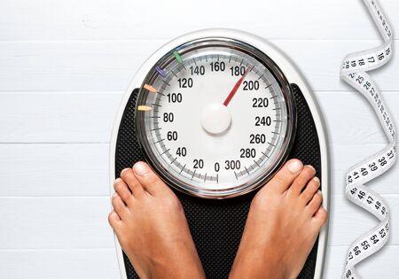 Bare female feet standing on bathroom scale Stock Photo