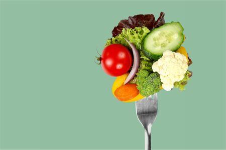 Verse rauwe groenten op vork op blauwe achtergrond