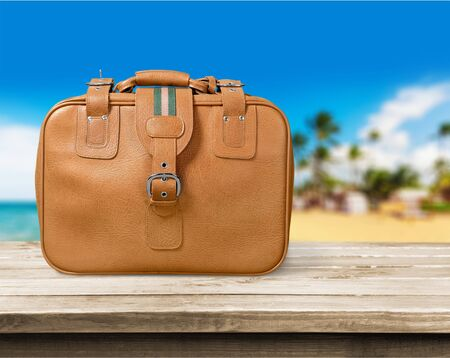 Travel bag on wooden floor and blue wall background