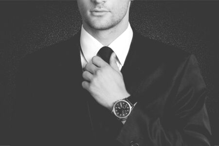 Businessman pointing at hand watch on grey wall background, close-up Stock Photo
