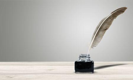 Federkiel mit Tintenfass auf Schreibtisch