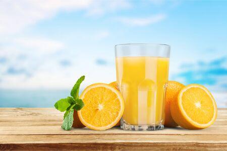 Succo d'arancia e fette d'arancia su sfondo Archivio Fotografico