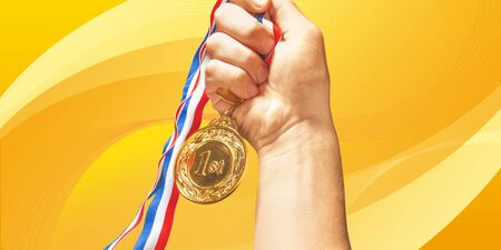 Gold medal with ribbon in hand on Imagens