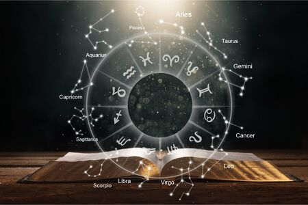 Close up of glowing book with zodiac wheel. Magic and astrology concept. Double exposure