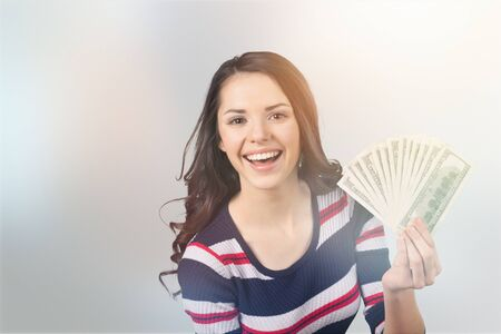 Pretty young woman holding money banknotes on background Stock Photo