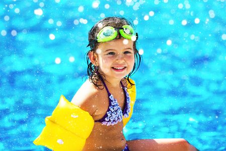 Beautiful girl in sunglasses at swimming pool in summer time