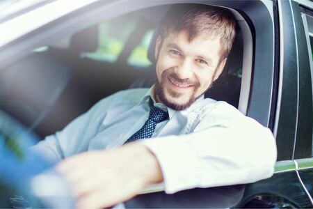 Young happy man in car smiling - concept of buying car