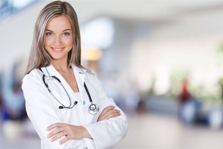 Attractive young female doctor with blurred hospital Фото со стока