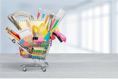 Stationery objects in mini supermarket cart on