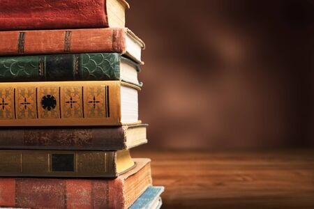 Colección de libros antiguos en el escritorio de madera