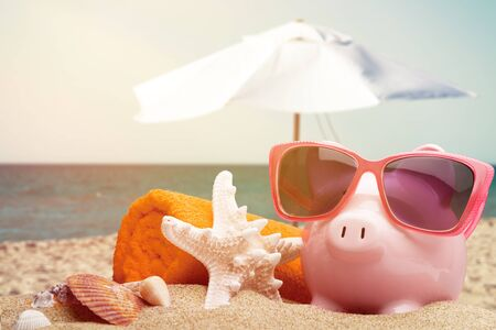 Pink piggy bank with sunglasses on beach