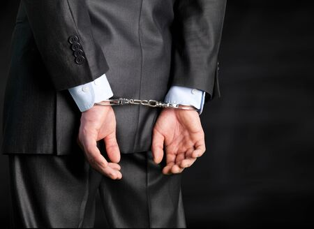 Cropped image of male hands in handcuffs behind his back Standard-Bild - 124542339