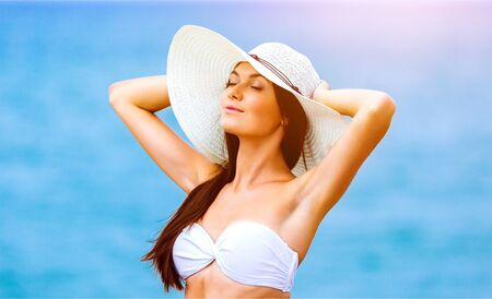 Beach woman happy on travel vacation holidays in bikini on by blue ocean sea at tropical resort. Cheerful smiling excited mixed race girl wearing sun hat laughing full of joy looking at camera Imagens