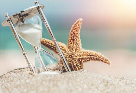 Hourglass and seastar on sandy beach