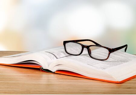 Black reading glasses and book