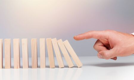 Male hand ready to push domino