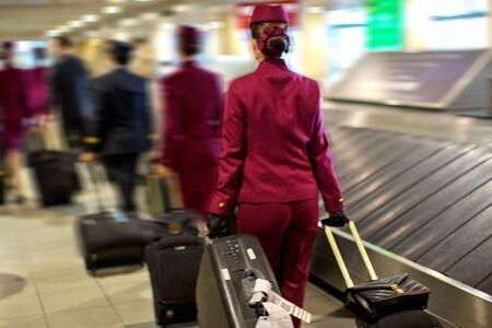Equipaggio di cabina in un aeroporto che trasporta i propri bagagli