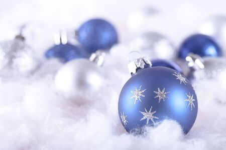 Blue and White Christmas Baubles on the Wadding on the Grey Background