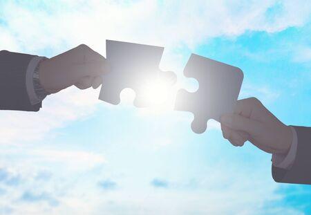 Hände setzen Puzzleteile Standard-Bild