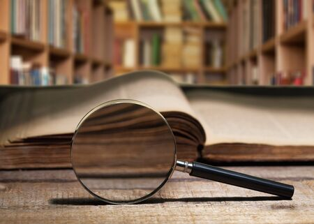 Vintage book and magnifying glass on wooden background Imagens