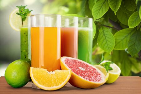 Orangensaft und Orangenscheiben im Hintergrund