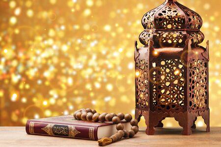 Trois mois.Livre saint islamique Coran avec chapelet sous une lumière douce sur fond blanc. Notion de ramadan.