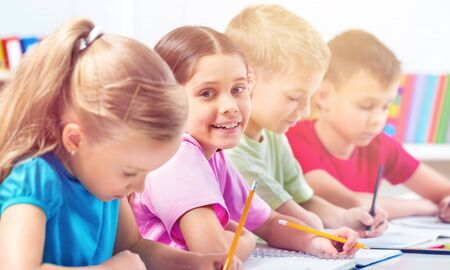 School Children in the Classroom Writing  Drawing Stock Photo