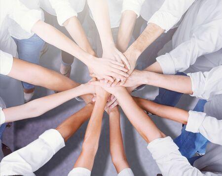 Groep mensen die handen bij elkaar stapelen