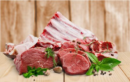 Fresh raw meat with vegetables on brown wooden table at wooden background