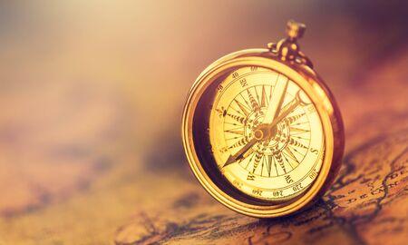 Alter goldener Kompass auf altem Kartenhintergrund, Vintage-Ton mit Kopienraum für Text.