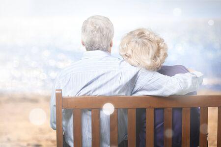 Portrait of happy senior couple in green blurred park background, bokeh