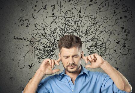 Trauriger junger Mann mit besorgtem, gestresstem Gesichtsausdruck und Gehirn, das in Fragezeichen in Linien zerfällt. Obsessives zwanghaftes, adhd, Angststörungskonzept Standard-Bild