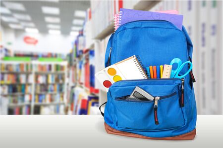 Open blue school backpack on a wooden desk and bokeh background.
