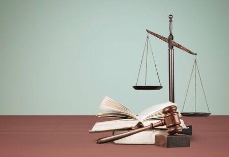Bilancia della giustizia e libri e martelletto di legno sulla tavola. Concetto di giustizia